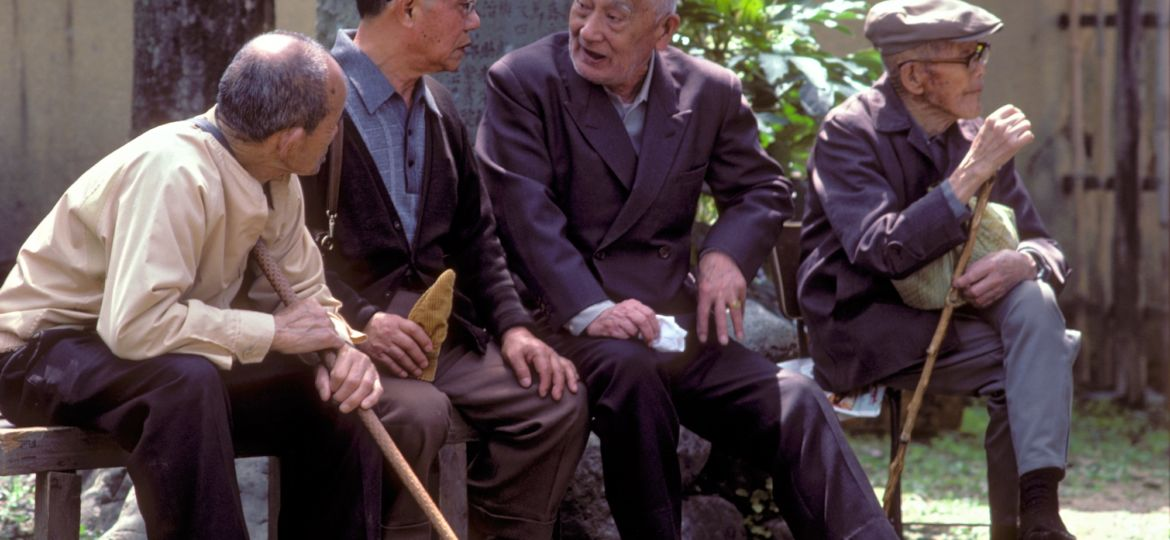 A group of elderly men sitting on a bench on a sunny day to discuss life in the past, present and future
